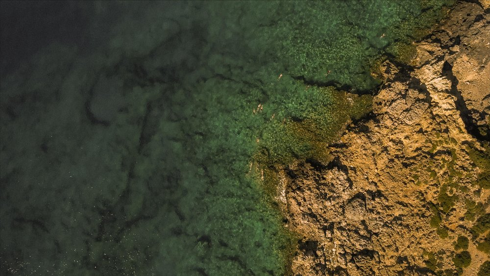 Drone shot of a man swimming in Loutro, Crete