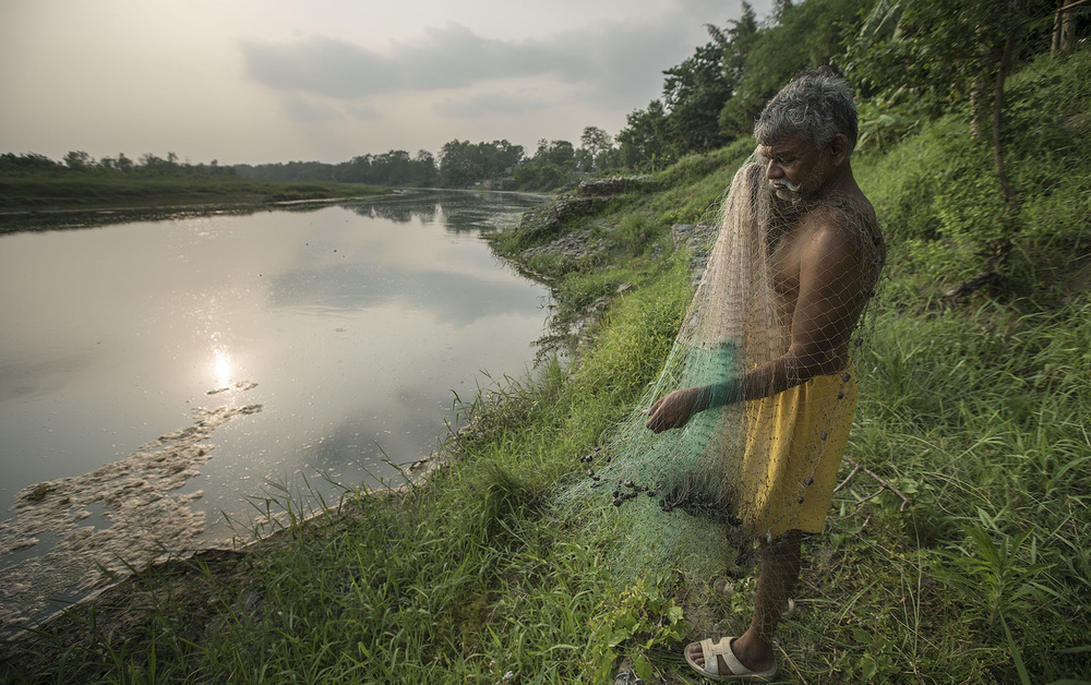 A local fisherman prepares his nets to fish in the Rapti river of Chitwan National Park.