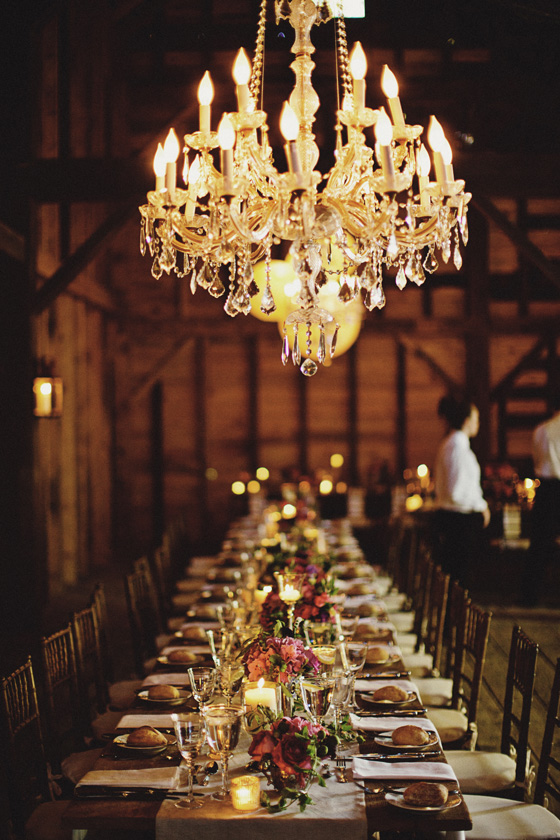 chandelier hanging in vintage restored Dutch barn over long wooden tables