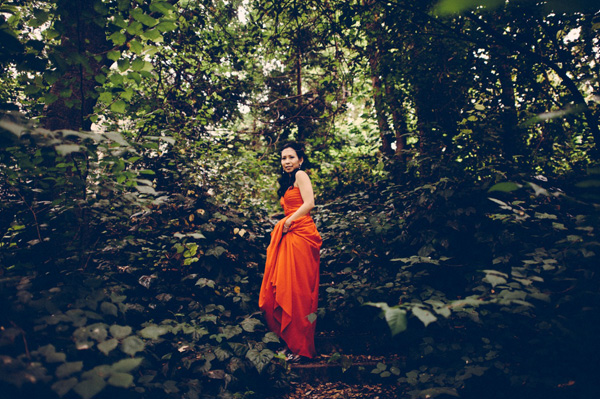 Bride standing in forest in red dress