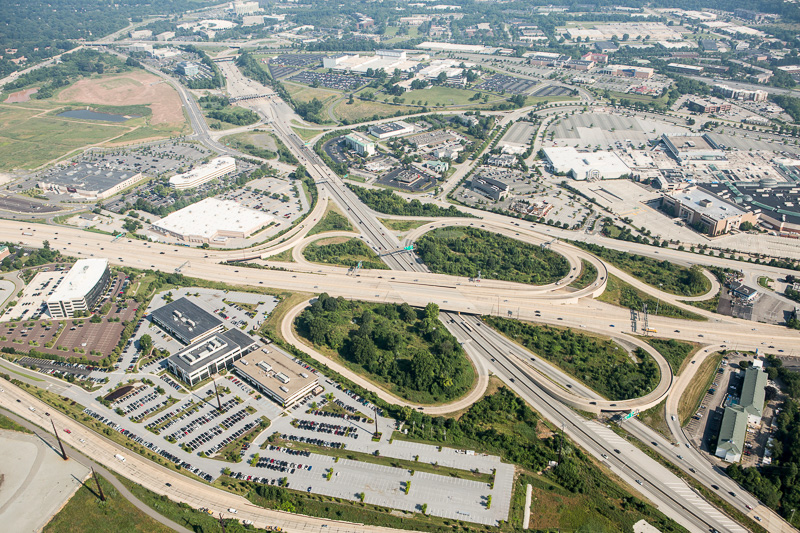 A wide view from above highlights suburban America's highways, shopping malls, and office buildings.