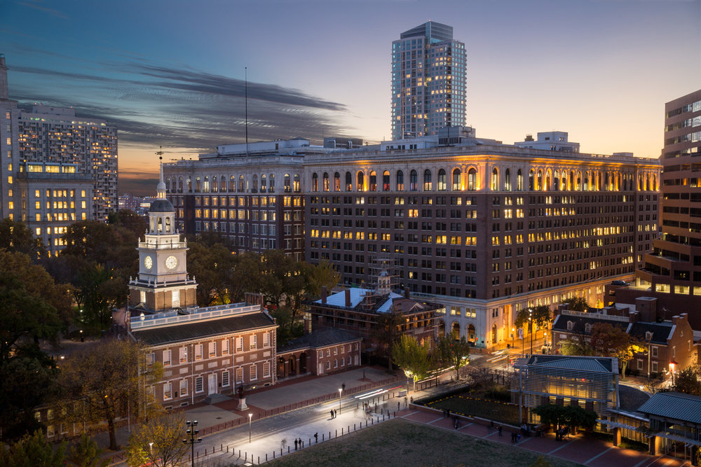 This Philadelphia twilight view shows the proximity of Public Ledger Building's (12 story building on right) to world famous Independence Hall with the steeple.