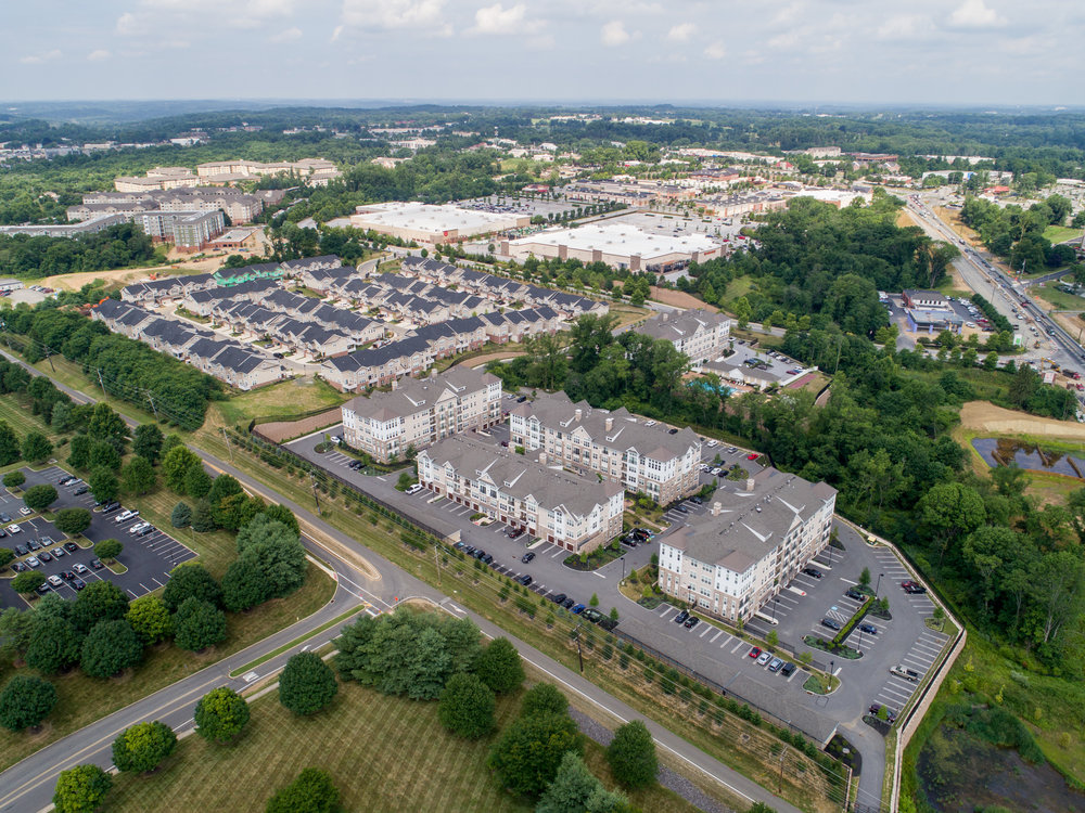 Drone as helicopter – entire apartment complex, with townhouses and retail in the distance.