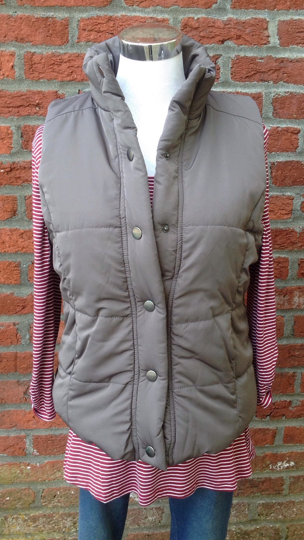 Grey snap front puff vest with side pockets and shearling lining, $48