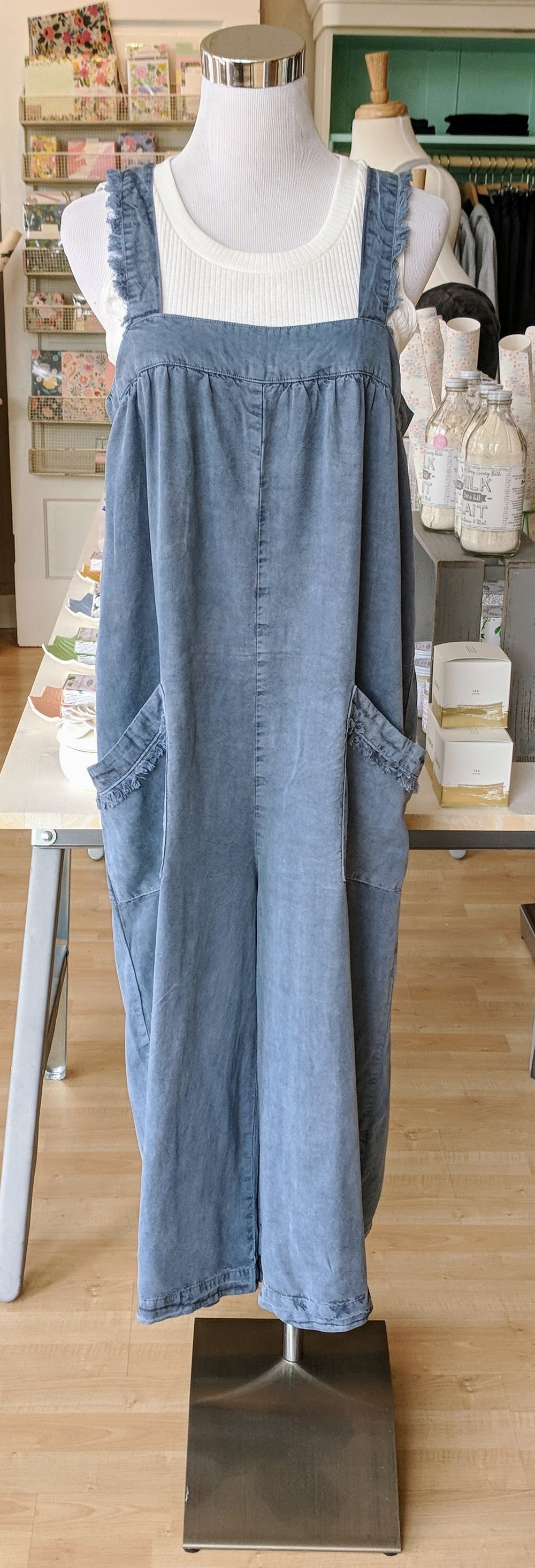 Blue distressed jumpsuit with back buttons.