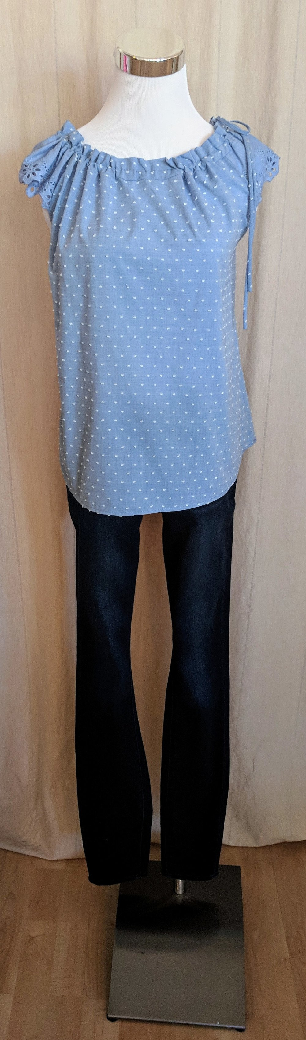 Light blue sleeveless top with tie detail on collar.