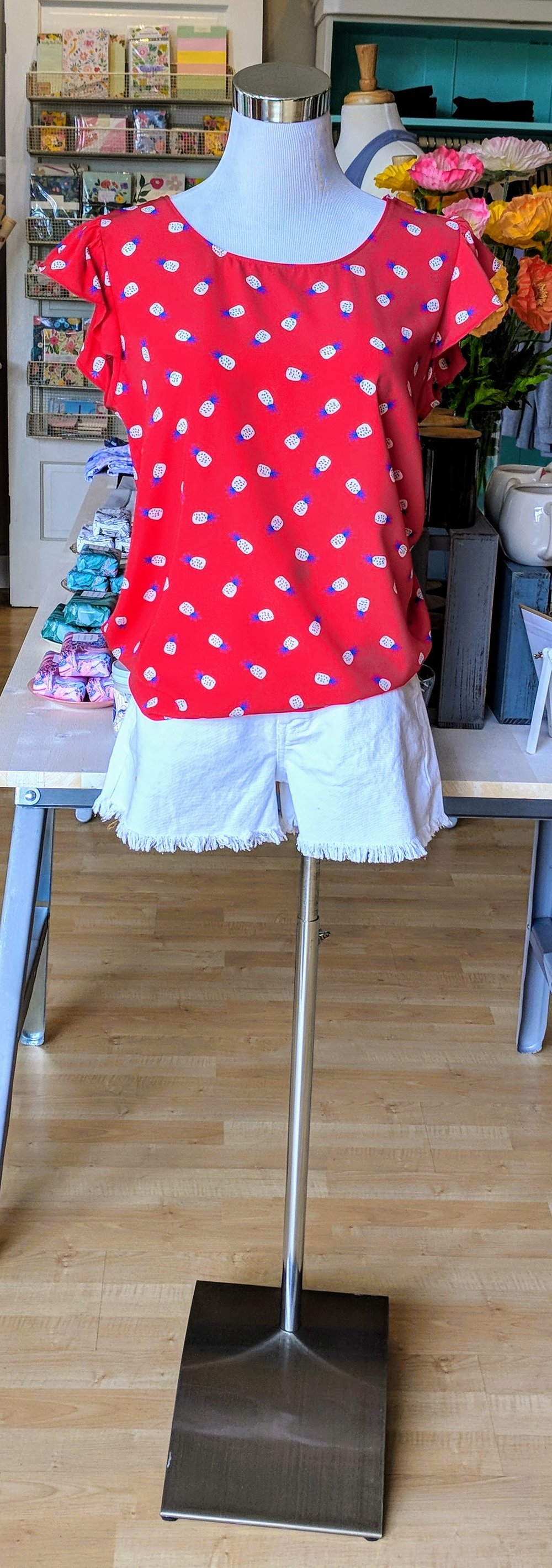 Coral pineapple top with flutter sleeve.