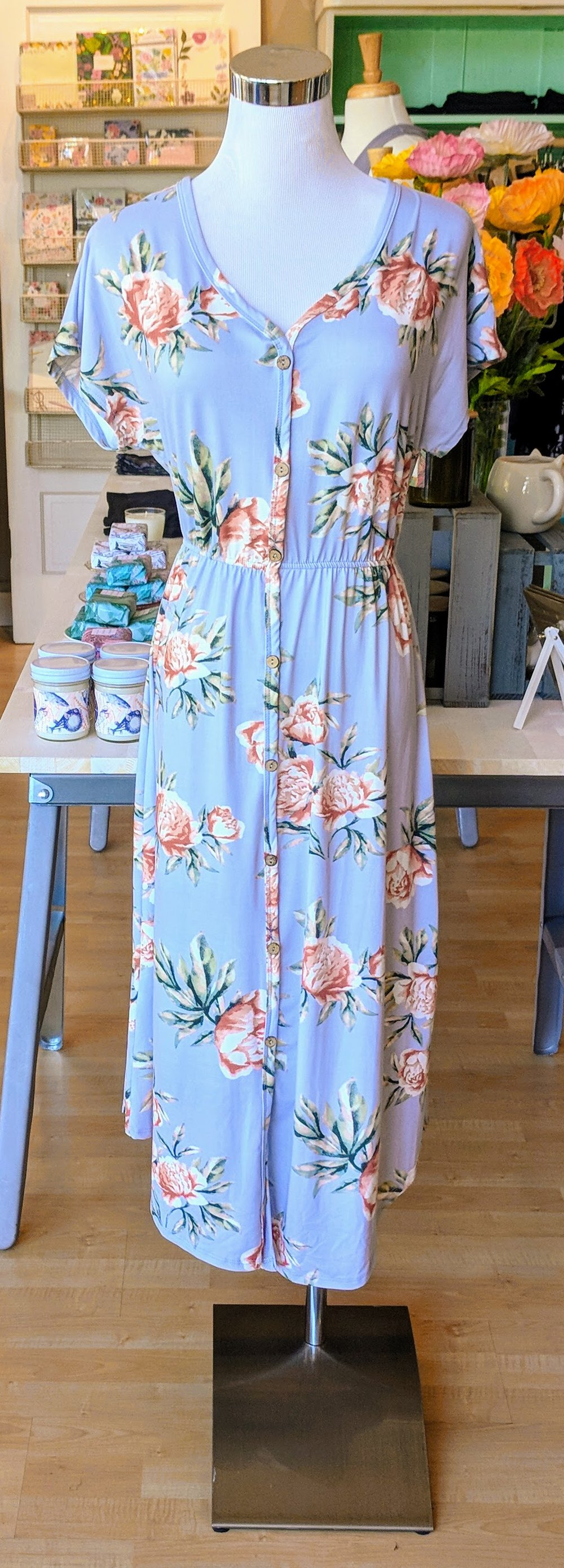Pastel floral midi dress with button detail front.