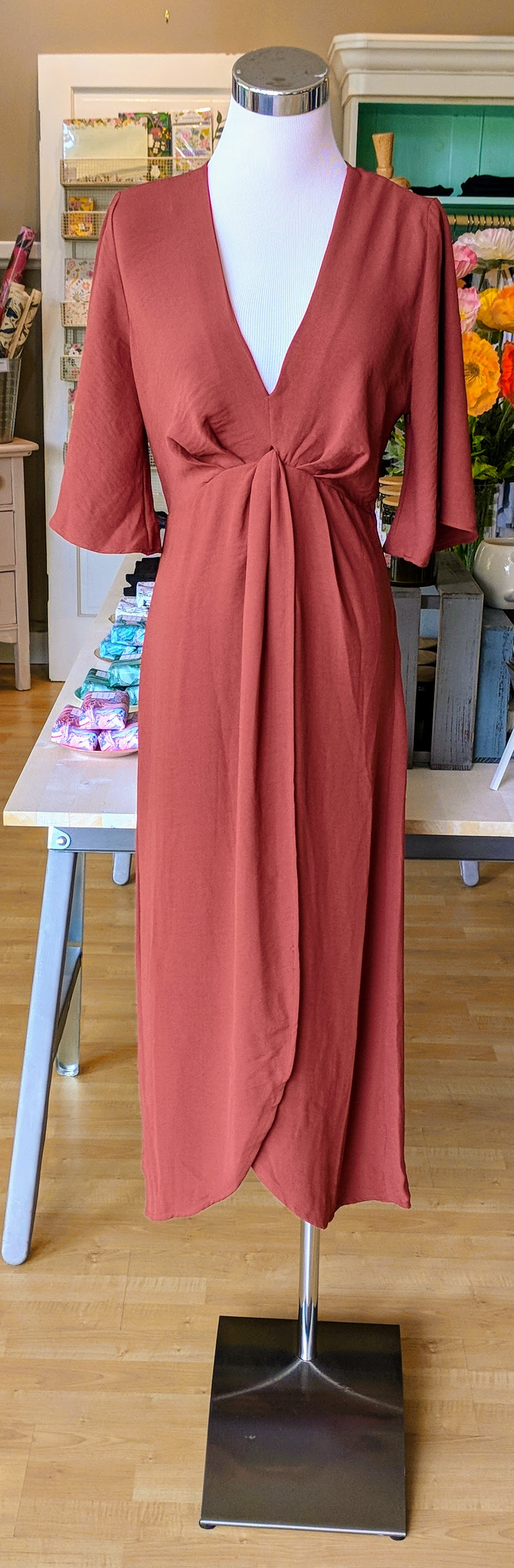 Brick color midi dress with fly away sleeve and knot detail on front.