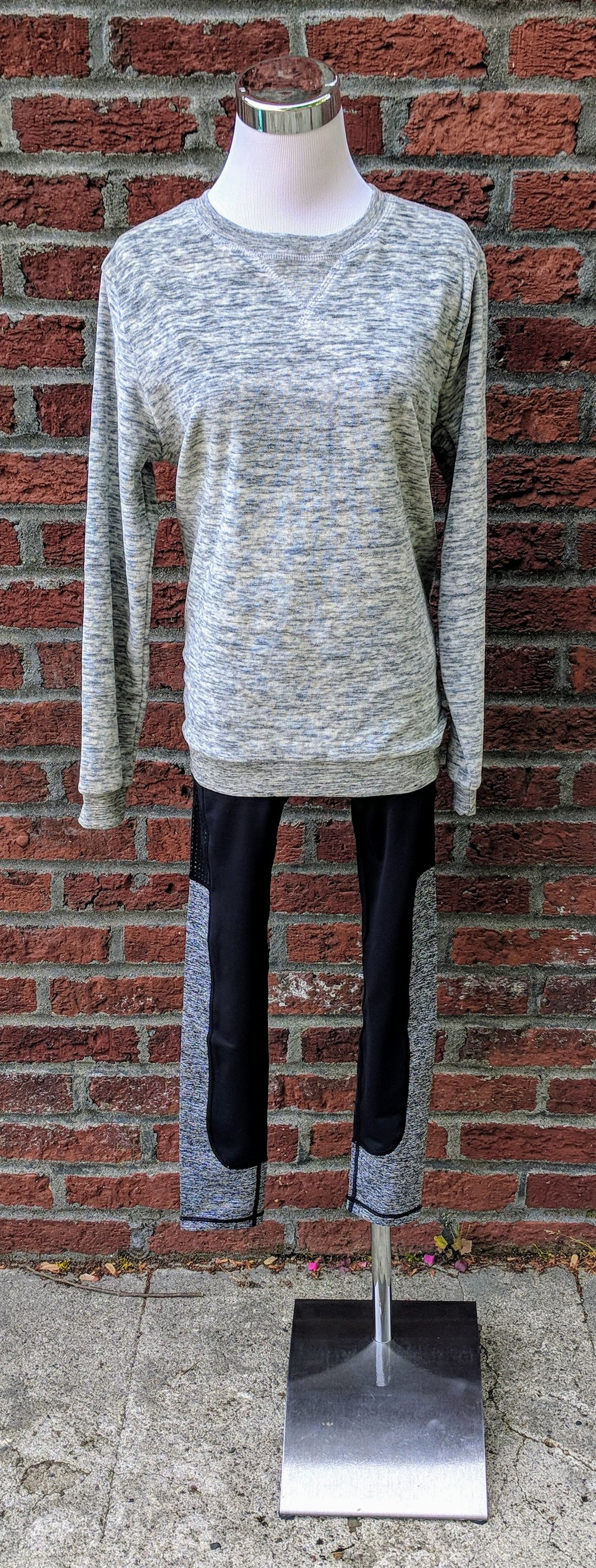 Grey cozy long sleeve sweater paired with black leggings with cut out details on legs.