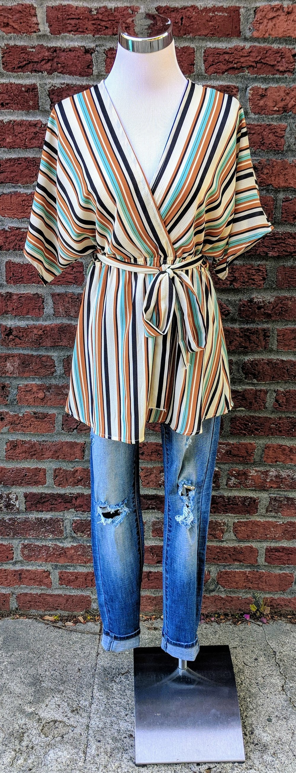 Multi-color stripe dolman top with cinched waist and tie detail.