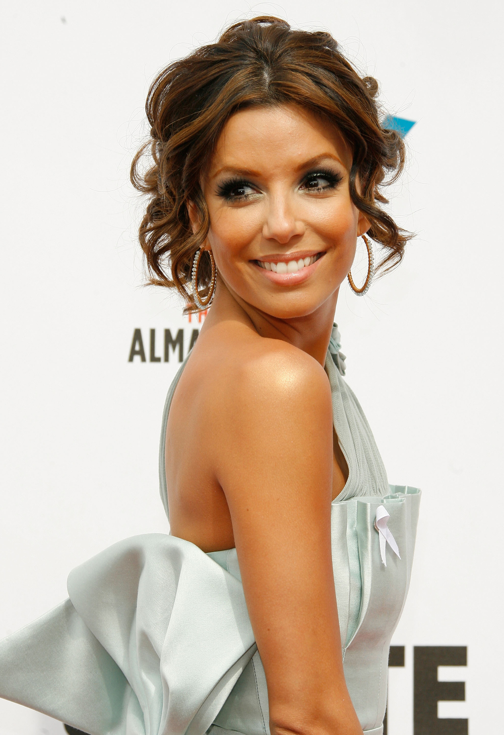 Eva Longoria wearing Simon Alcantara's 14kt yellow gold hoops hand woven with blue topaz at the Alma awards