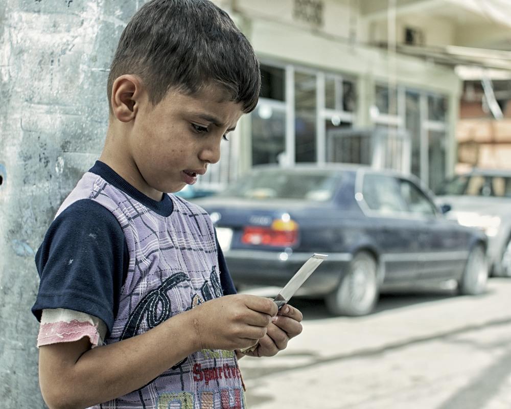 un enfant au kurdistan qui regarde son polaroid se développer