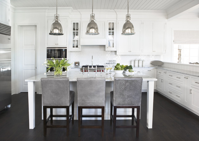 Chrome lights, grey leather chairs and stainless fridge all pop in this white kitchen Via  McDougald Design