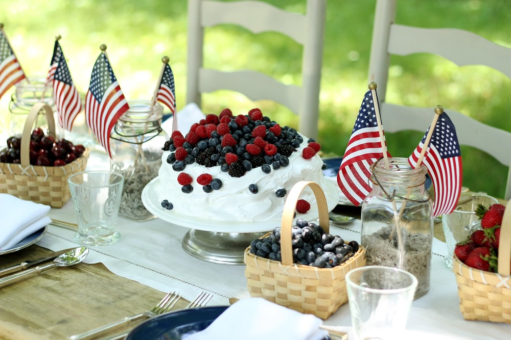 Lots of simple red, white and blue add to the table.  A white frosted cake with raspberries and blueberries.