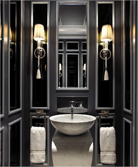 A chic mirror and lighting make for a glamorous powder room. The perfect combo of colors: steel grey, ebony black, and brilliant whites.