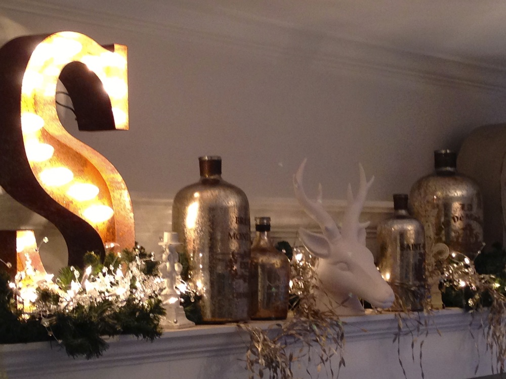This garland is on the shelf over my TV cabinet.  Lights, garland, vintage style mercury glass and white deer evoke a vintage look.