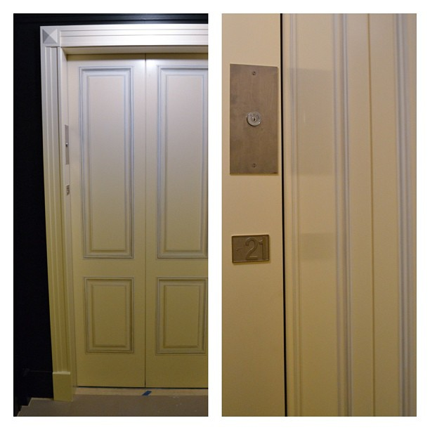 Trompe l'oeil painting of applied molding on elevator doors.
