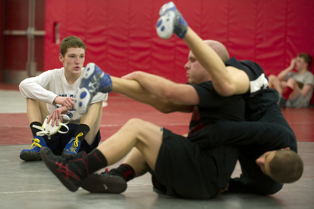 Wilson wrestler Jaryd Flank, left, watches as Parkland wrestling assistant coach, and former Wilson Area High School state champion, Jeremy Hartrum, center, demonstrates a move on Northwestern Lehigh wrestler Jarret White, right, at Parkland High School. Express-Times Photo | MATT SMITH