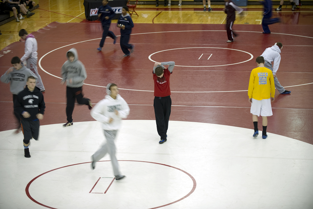 Wilson wrestler Jaryd Flank, center, stretches on the mat as other wrestlers run laps during warm-ups for the PIAA Class AA southeast regional tournament at Wilson High School. Express-Times Photo | MATT SMITH