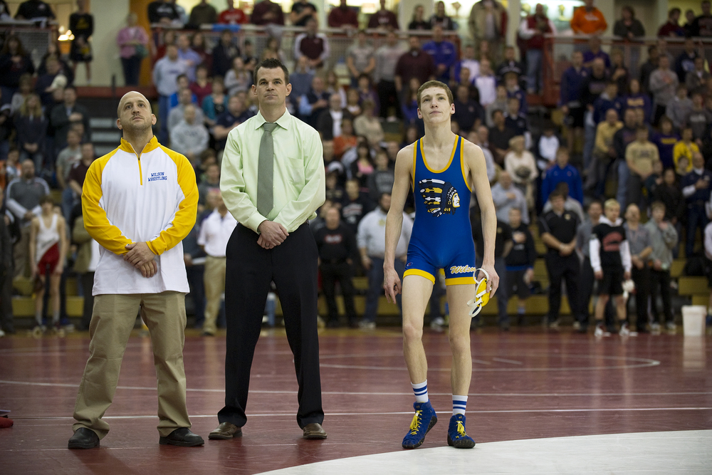 Wilson assistant coach Gary Rute, left, head coach Tom Mertz, center, and wrestler Jaryd Flank,  right, stand together during the playing of the National Anthem during  the PIAA Class AA southeast regional tournament at Wilson High School. Express-Times Photo | MATT SMITH