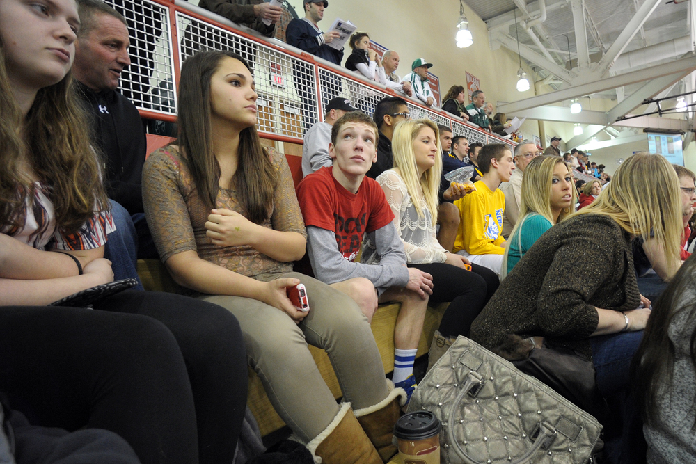 Wilson wrestler Jaryd Flank sits in the stands with family and friends after beating Trinity wrestler Chase Drawbaugh 4-3 in the preliminary round of the PIAA Class AA southeast regional tournament at Wilson High School. Express-Times Photo | MATT SMITH