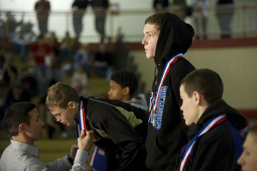 Bethlehem Catholic head coach and father of wrestler Luke Karam awards his son the gold medal after he defeated Wilson wrestler Jaryd Flank, right, 7-0 in the PIAA Class AA southeast regional finals at Wilson High School. Express-Times Photo | MATT SMITH
