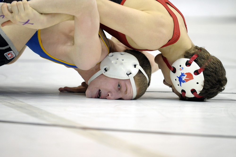 Wilson wrestler Jaryd Flank gets his face pressed against the mat by Southmoreland wrestler Austin Griffiths in the 106-pound weight class during the preliminary round of the 2013 PIAA Class AA wrestling championships at the Giant Center. Express-Times Photo | MATT SMITH