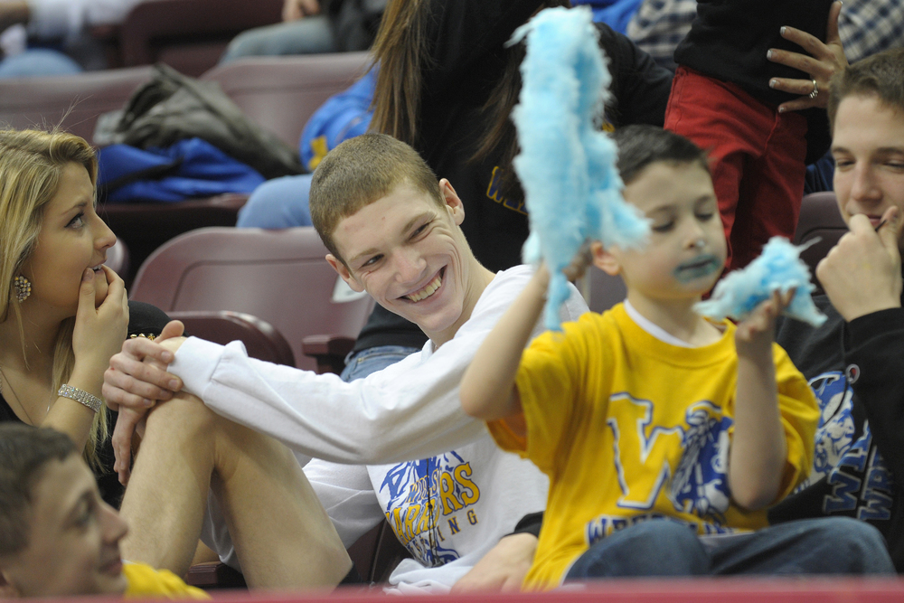 Wilson wrestler Jaryd Flank, left, laughs as Tino Micci, right, gets messy as he eats cotton candy during the 2013 PIAA Class AA wrestling championships at the Giant Center. Flank waits in the stands with family and friends for his consolation match following a 6-1 loss in the preliminary round to Soutmoreland wrestler Austin Griffiths. Express-Times Photo | MATT SMITH
