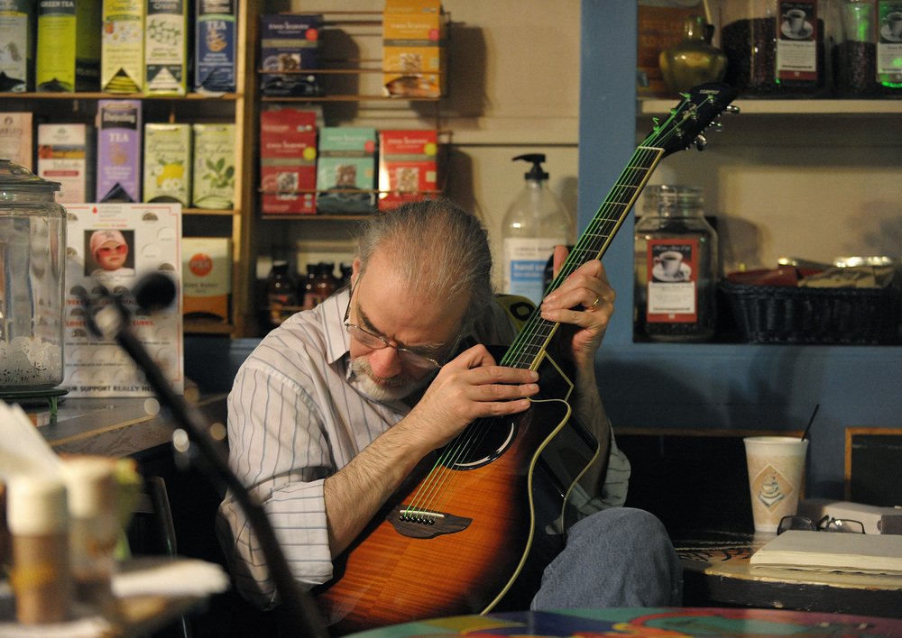 Richard Schneck, of Allentown, leans in to hear his guitar as he plays along with a performer during an open mic at Hava Java in Allentown. Express-Times Photo | MATT SMITH