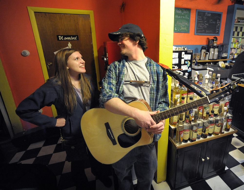 Amy Slahta, left, of Bethlehem, talks to Josh Klingman, right, of Allentown, as he gets ready to perform his set during an open mic at Hava Java in Allentown. Express-Times Photo | MATT SMITH
