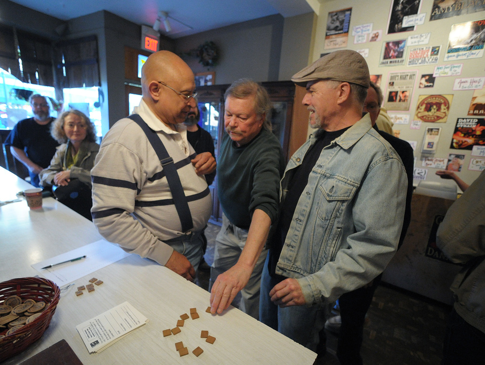 Volunteer Leon Bonam, left, stands by as Dave Fry, center, and Don Elliker, right, of Sparta, NJ, draw Scrabble tiles to determine an order of performance before an open mic at Godfrey Daniels in Bethlehem.Express-Times Photo | MATT SMITH