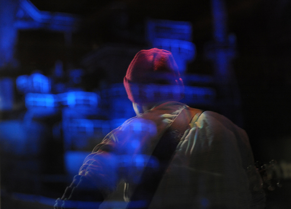The illuminated former blast furnaces of Bethlehem Steel are reflected as Mike Frank, of Stewartsville, performs during an open mic at the ArtsQuest Center at SteelStacks. Express-Times Photo | MATT SMITH