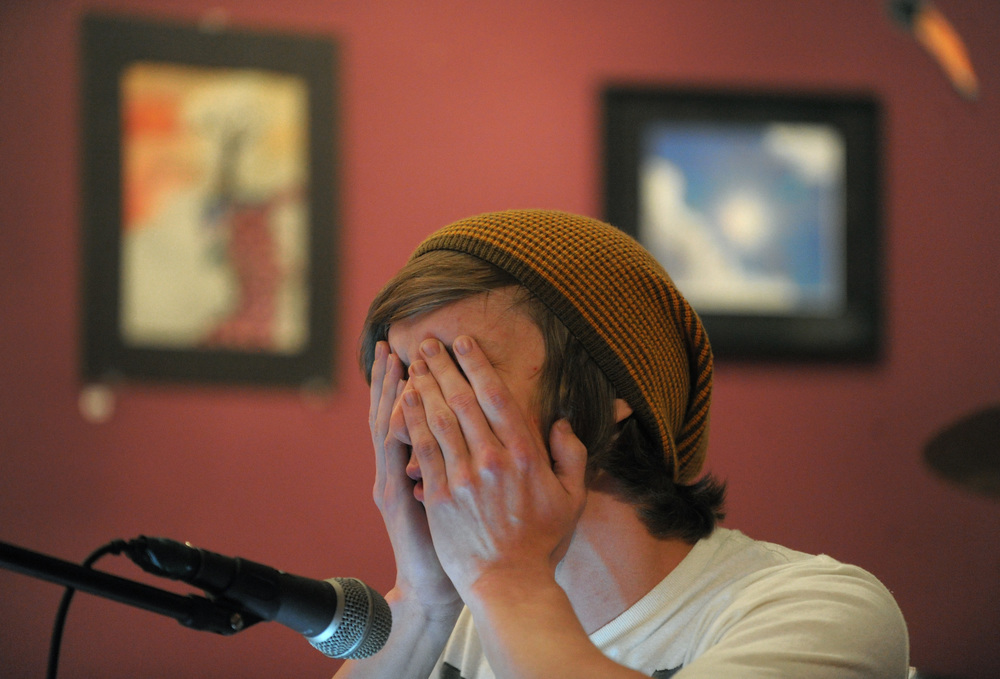 Jesse Morales, of Pocono Lake, holds his hands over his face as he performs a spoken word piece during an open mic at The Living Room in Stroudsburg. Express-Times Photo | MATT SMITH