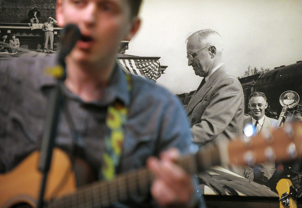 Cory Hobson, of Whitehall, performs in front of a large photograph of President Harry Truman during an open mic at The Wooden Match. Express-Times Photo | MATT SMITH