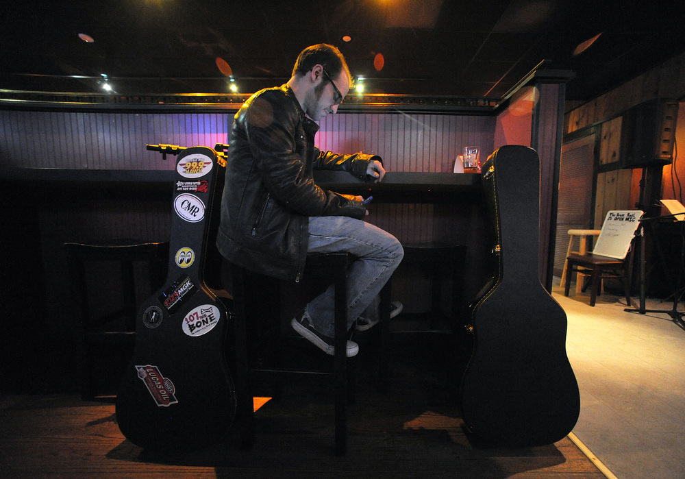 Mike Geroni, of Quakertown, checks his phone as he waits for his set during an open mic at The Brass Rail.Express-Times Photo | MATT SMITH