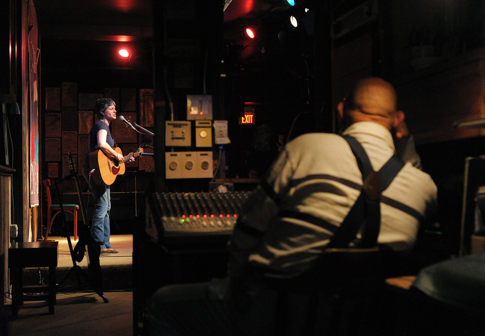 Musician and Godfrey Daniels President Dina Hall, left, performs on stage as long-time volunteer Leon Bonam, right, listens from the sound room during an open mic at Godfrey Daniels in Bethlehem.Express-Times Photo | MATT SMITH