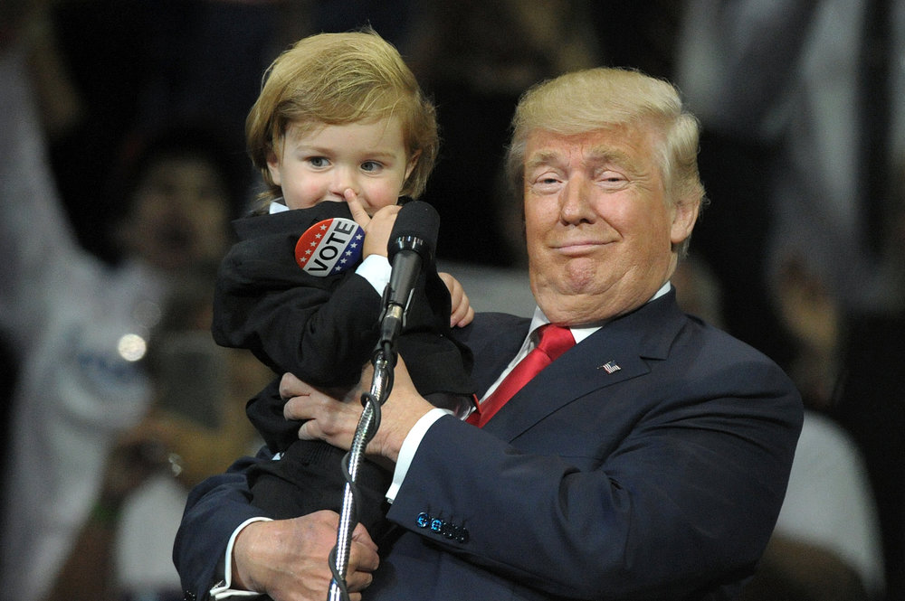 """Baby Trump"" Hunter Tirpak, 2, is asked by Republican Presidential nominee Donald Trump if he wants to go back to his parents or stay with Trump. Tirpak responded simply ""Trump."" This was during a rally at Mohegan Sun Arena in Wilkes-Barre, Pennsylvania. (Photo by Matt Smith)"