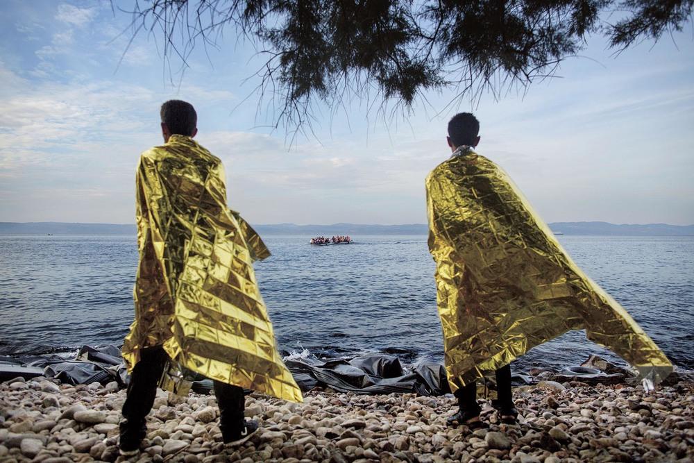 Nok en gummibåt med flyktninger stevner mot Lesbos. To syriske ungdommer er allerede fremme, iført gule «foliefrakker» for holde på varmen. Søkkvåte, men lykkelige. Foto: ESPEN RASMUSSEN