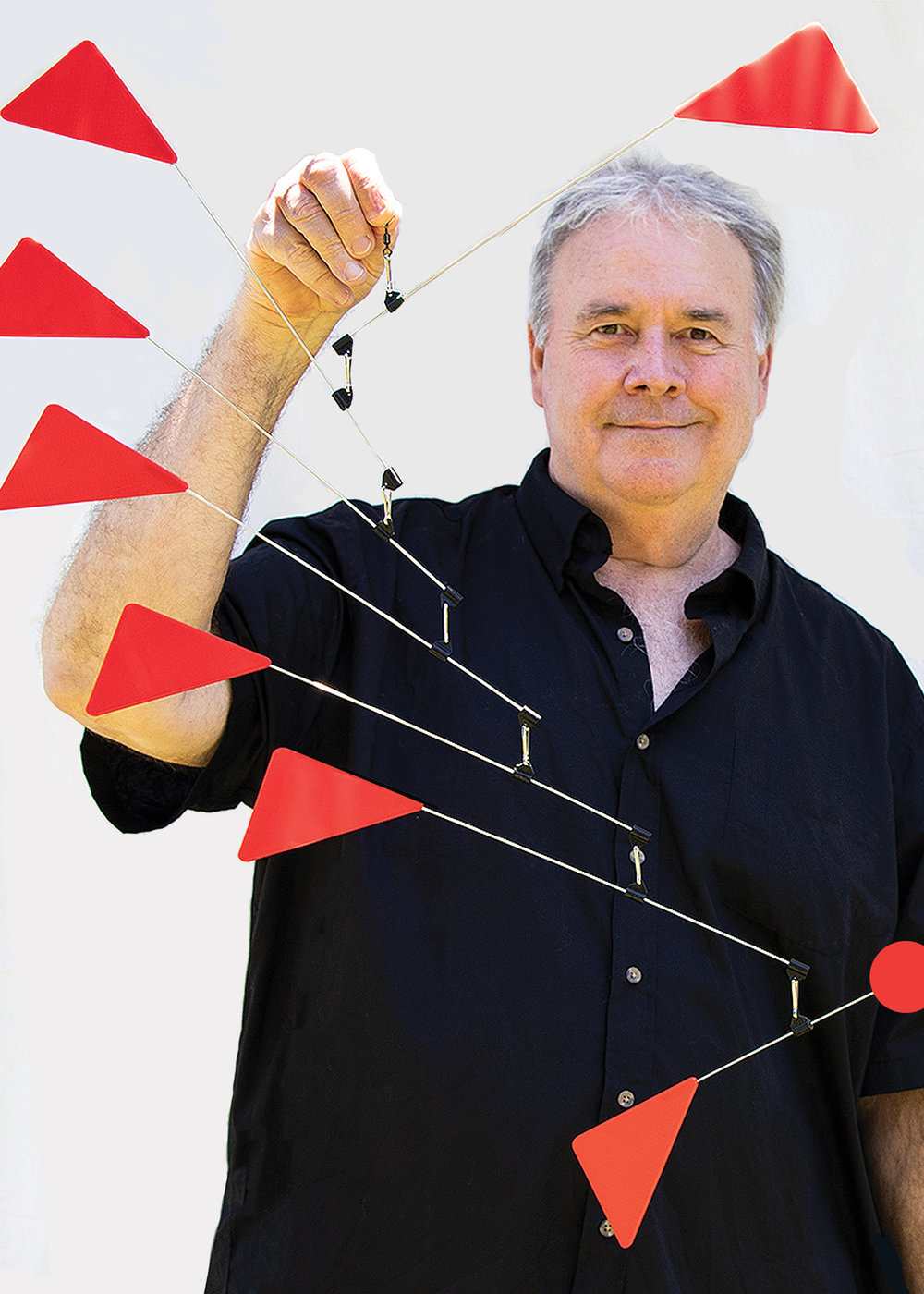 Richard John Jenkins holding Triangles Futura Mobile