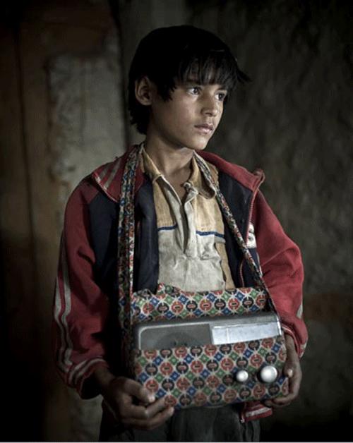 PADAM BANADUR SHAHI, 13 ans. Ecolier. Il n'a pas encore l'âge d'avoir une radio, alors il emprunte quotidiennement celle de son père. Il économise depuis plusieurs mois et dès qu'il aura la somme suffisante, il ira dans une grande ville pour s'acheter sa propre radio.    © Stéphane Remael