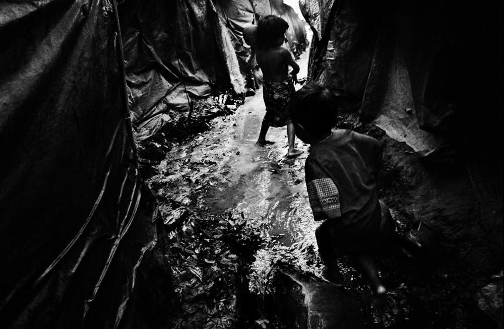 Deux enfants jouent dans une allée inondée du camp de Tal. Chaque année, pendant la mousson, l'eau qui vient des collines qui entourent le camp se mêle à celle des égouts, et y déverse immondices, carcasses, débris. (2006)  © Greg Constantine, Exiled To Nowhere