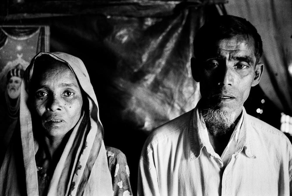 Pour échapper à leur situation désespérée au Bangladesh, des milliers de Rohingya essaient de trouver des passeurs qui les emmèneraient par bateau jusqu'en Thaïlande ou en Malaisie. Début 2009, les autorités thaïlandaises ont rejeté à la mer sans eau ni nourriture tous ceux qui tentaient d'entrer dans les eaux territoriales. La plupart ont disparu, comme le fils ce ce couple, dont ils n'ont plus jamais eu de nouvelles depuis son départ en bateau en décembre 2008  © Greg Constantine, Exiled To Nowhere