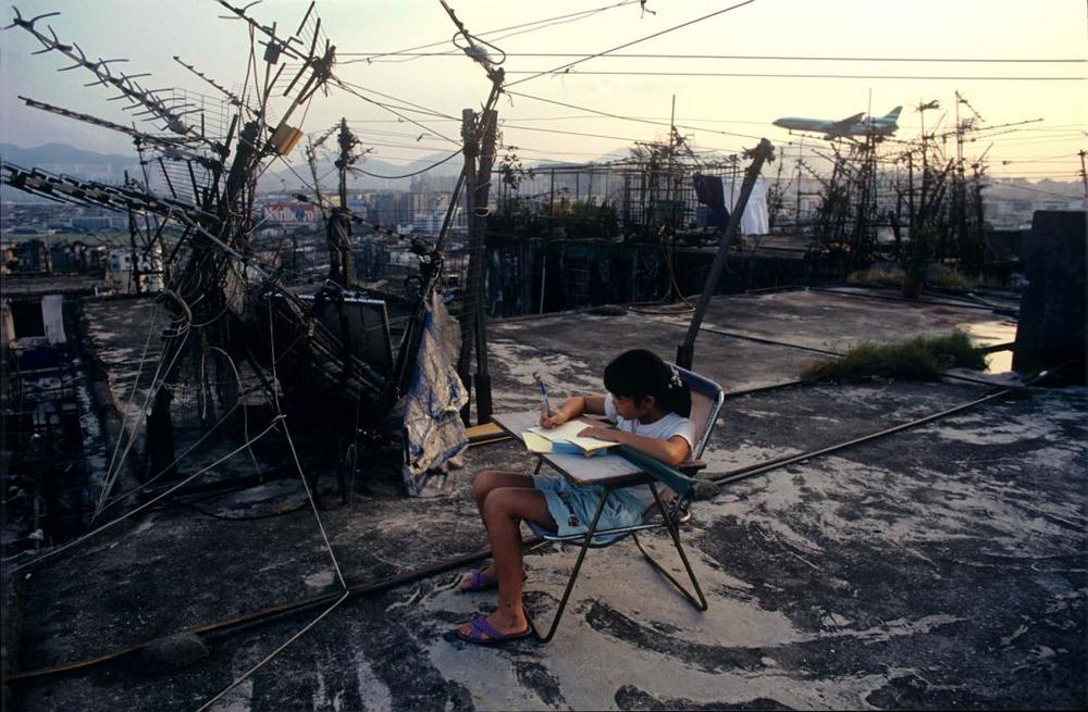 Student doing homework on Walled City rooftop, 1989  © Greg Girard