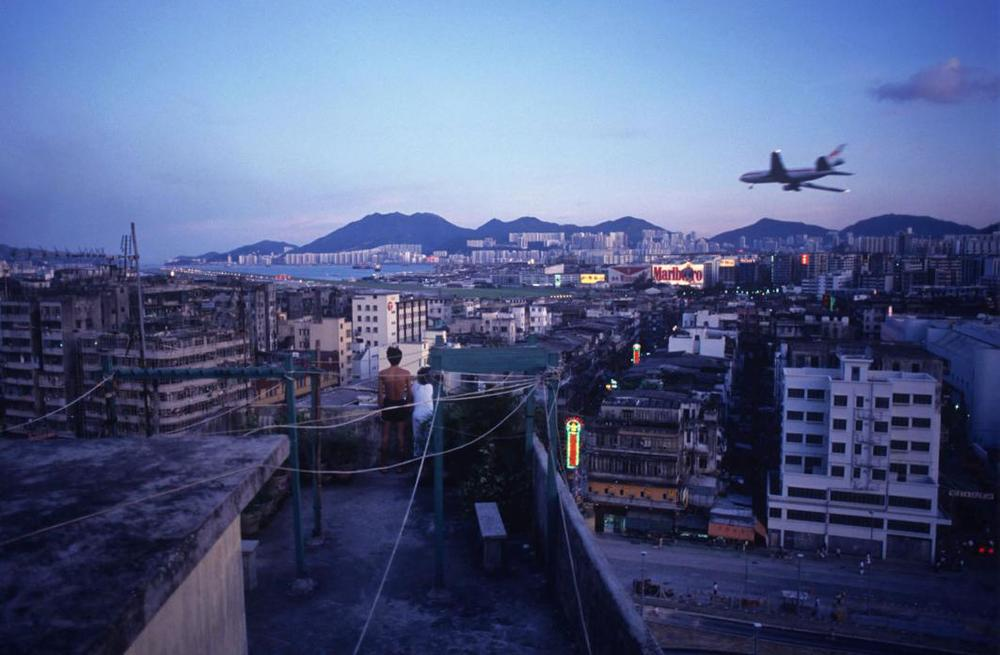 Watching aircraft land at Kai Tak Airport from Walled City rooftop, 1990  © Greg Girard