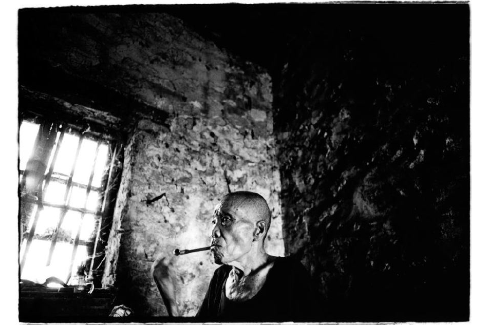 """Chine, Duan, 14 juin 2007. Un villageois de 73 ans fume. La vue atteinte, ses bras et ses jambes atteintes par la maladie, cet homme ne se connait plus de famille, comme beaucoup des ex-lépreux : """"Je voudrais revoir ma famille, mais je ne sais pas où ils vivent. Et même si je les voyais, ils ne voudraient pas de moi...""""    Kosuke Okahara , Vanishing existence."""