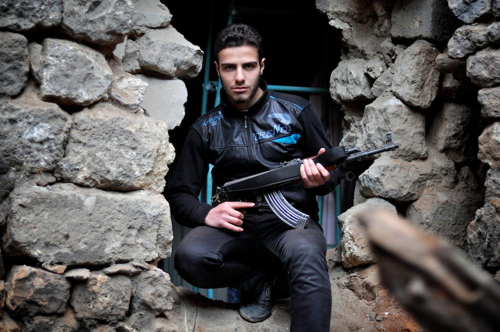 """Muhammed (Surnom : """"Docteur"""") – 19 ans   Muhammed était étudiant en informatique avant de suspendre ses études à cause de la guerre. Il se bat pour une Syrie libre parce qu'il a été jeté en prison et torturé suite à la protestation contre le régime d'Assad et parce que sa maison a été frappée et détruite par un mortier. Il espère finir ses études lorsque la Syrie sera revenue à la paix, et peut-être travailler dans la nouvelle Armée syrienne pour reconstruire le pays. """"Ce que le peuple veut, sera. L'injustice ne restera pas.""""    ©Cengiz Yar Jr ,The Young Men of the Free Syrian Army"""
