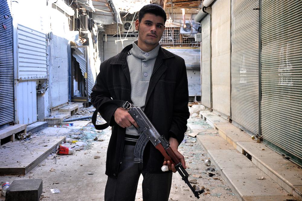 """Makmood – 19 ans   Avant la guerre, Makmood travaillait le métal dans la construction et vendait des voitures. Il se bat aux côtés de l'Armée Syrienne Libre pour la défense de l'Islam. Récemment blessé par un mortier atterrissant dans sa maison, Makmood a un éclat d'obus dans le torse et son doigt est très infecté. Il parle très peu anglais mais souhaiterait aller vivre un jour en Amérique. Ses rêves d'Amérique sont cependant tempérés par la réalité de vie quotidienne à Alep ; Makmood constate calmement: """"Peut-être qu'après la guerre, je ne serai plus en vie"""" .   ©Cengiz Yar Jr ,The Young Men of the Free Syrian Army"""