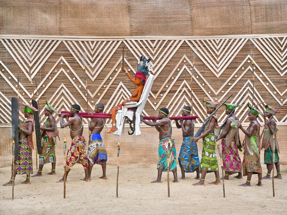"""«Ensansa: bôpápá boutíka nd'ípoy, mí nyúme nd'ókonda w'élóba, mí ngóyé, basómi báyânkùmá l'´ndóki nd'âpèke». Song: papas tipoy put me in, me I go into eloba forest, me I come, all assistants with rifles on shoulders.  Traditionellement, un chef local (nkúmu) se déplace sur un """"tipoy"""" accompagné par son armée. Wale Oyombé (22 ans, mariée, cinq ans de séclusion, mère d'Angela) chante qu'elle est fière d'être considérée comme un patriarche parce qu'elle a respecté le tabou sexuel pendant sa longue séclusion de cinq ans. Comme un chef, elle est portée sur un tipoy. Elle compare ses assistants à des soldats qui ont assuré sa survie et sa sécurité tout ce temps.   Patrick Willocq"""