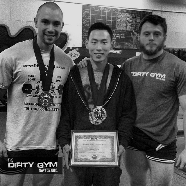"""123# Sung Kim holds up his """"Mens Overall Best Lifter"""" Award with The Dirty Gym Coaches Matt Swartout and Marcus Mucheck."""